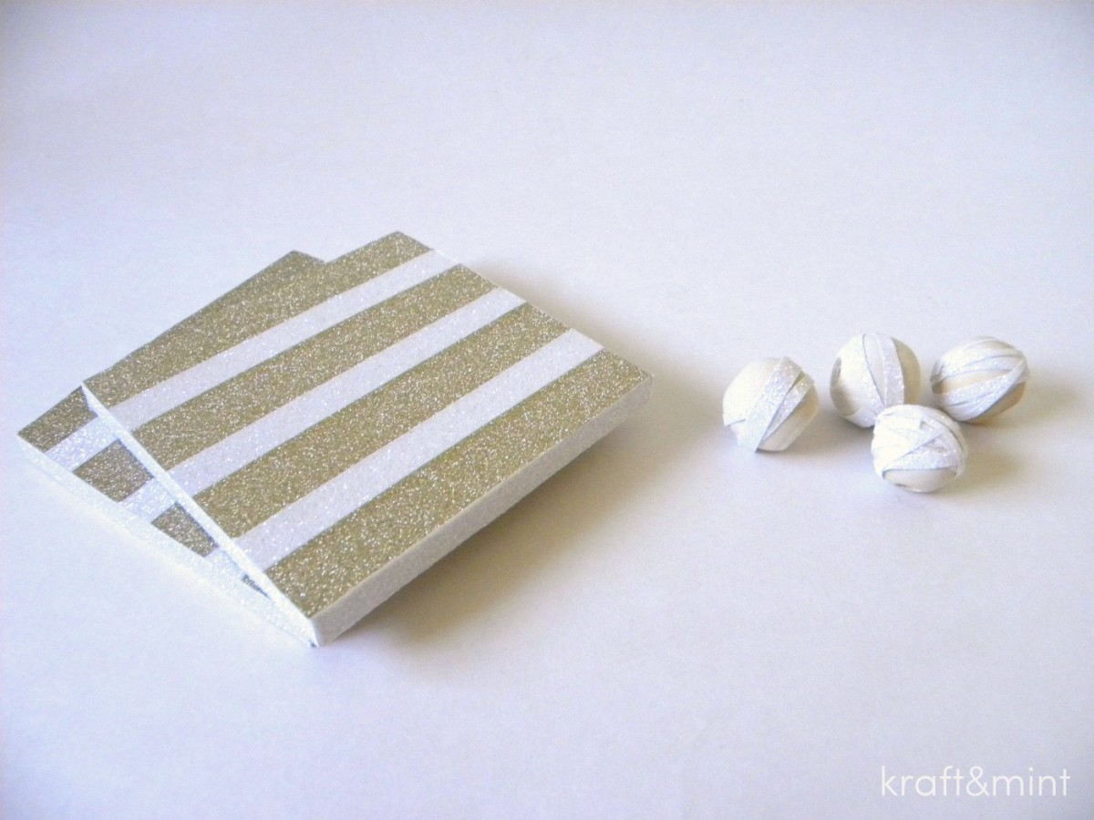 Coaster covered with gold sparkle tape and white glitter tape. Wood beads covered with very thin strips of white glitter tape.